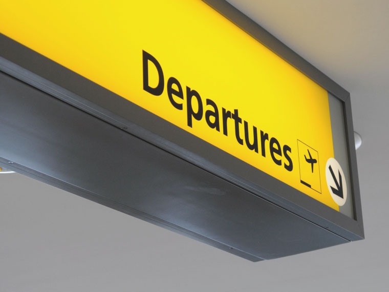 a departures sign at a airport provided by Addison Lee